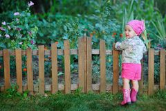 Little girl in pink boots near the fence Stock Images
