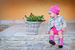 Little girl in pink boots sitting on the steps Royalty Free Stock Image