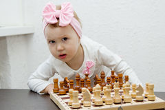 Little girl with pink bow playing chess stock photography