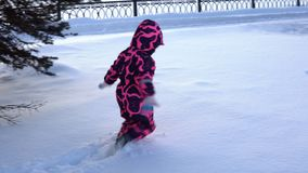 A child in overalls walks through snowdrifts. A little girl in a pink children`s winter overalls walks through high snowdrifts through the city park stock video