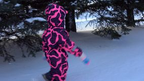 A child in overalls walks through snowdrifts. A little girl in a pink children`s winter overalls walks through high snowdrifts through the city park stock footage