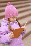 Little girl in pink coat reads book Royalty Free Stock Photography