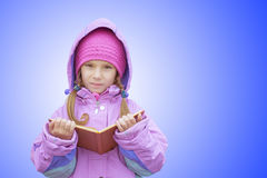 Little girl in pink coat reads book Royalty Free Stock Images