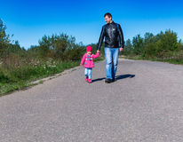 Little girl in a pink coat walking the park. she holding the hand of  high handsome man. daughter and dad. Stock Photo