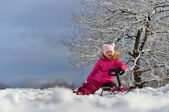 A little girl in a pink down jacket sitting on a sled under a tree in the snowy winter. stock photography