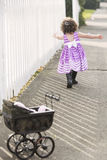 Little girl in pink dress chasing soap bubbles royalty free stock photo