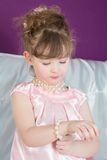 Little girl in a pink dress corrects beads. Beautiful little girl in a pink dress corrects beads from pearls royalty free stock image