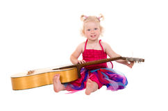 Little girl in a pink dress playing guitar Royalty Free Stock Image