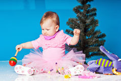 Little girl in pink dress plays near New Year tree Stock Image
