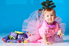 Little girl in pink dress plays near New Year tree Royalty Free Stock Photos