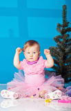 Little girl in pink dress plays plays with rattle Royalty Free Stock Images