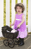 Little girl in pink dress with a pram Stock Images