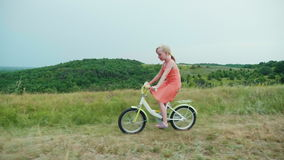 A little girl in a pink dress rides a bicycle in the countryside. Happy carefree childhood. Steadicam shot stock video