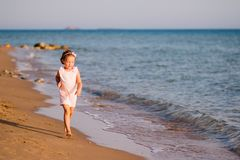 Little girl in pink dress running on the beach at sunset.View in motion.Happiness,vacation, fun.happy cute child runs on Royalty Free Stock Images