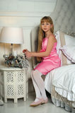Little girl in a pink dress sitting on a bed Stock Photography