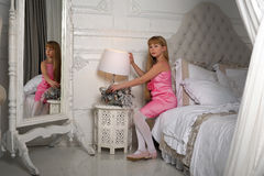 Little girl in a pink dress sitting on a bed Stock Images