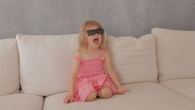 A little girl in a pink dress sitting on the couch attentively and emotionally watching TV in 3D glasses stock video