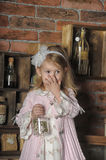 Little girl in a pink dress sitting on retro kitchen Royalty Free Stock Photography