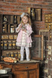 Little girl in a pink dress sitting on retro kitchen Royalty Free Stock Photos