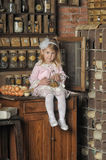 Little girl in a pink dress sitting on retro kitchen Stock Photos