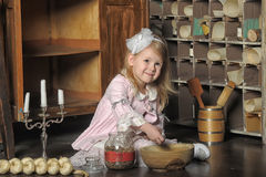 Little girl in a pink dress sitting on retro kitchen Royalty Free Stock Images