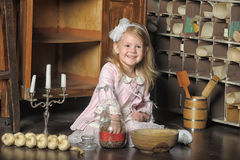 Little girl in a pink dress sitting on retro kitchen Royalty Free Stock Image