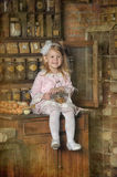 Little girl in a pink dress sitting on retro kitchen Stock Photo