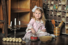 Little girl in a pink dress sitting on retro kitchen Stock Image