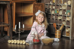 Little girl in a pink dress sitting on retro kitchen Stock Photography