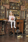 Little girl in a pink dress sitting on retro kitchen Royalty Free Stock Photo