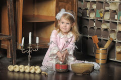 Little girl in a pink dress sitting on retro kitchen Stock Images