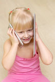 Little girl in a pink dress smile and talking on cell phone and Royalty Free Stock Images