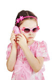 Little girl in a pink dress talking by the toy phone Royalty Free Stock Photo