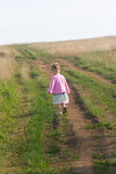 Little girl in a pink dress walking along a road Royalty Free Stock Photo