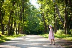 Little girl in a pink dress walking down Stock Image