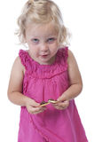 Little girl in pink eating a biscuit, isolated on white Royalty Free Stock Photo