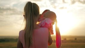 Little girl in pink festive dress holding big plush bunny toy at sunset. Silhouette of a child with a toy. Textile stock footage
