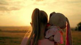 Little girl in pink festive dress holding big plush bunny toy at sunset. Silhouette of a child with a toy. Textile stock video