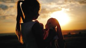 Little girl in pink festive dress holding big plush bunny toy at sunset. Silhouette of a child with a toy. Textile stock video footage