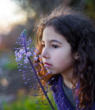 Little girl pink flower. Little girl smelling a purple flower Stock Photography