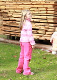 Little girl in pink in front of wood Stock Image