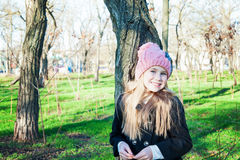 Little girl in pink hat and jacket standing near tree, park Royalty Free Stock Photo
