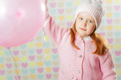 Little girl in a pink hat and a sweater Royalty Free Stock Image
