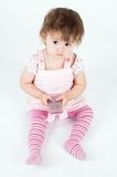 Little girl in pink holding mobile. Isolated on white Stock Photo