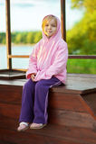 Little girl in pink jacket sitting Royalty Free Stock Images