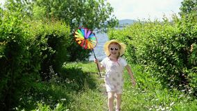 A little cute girl playing with a colorful pinwheel in the garden on a warm day. A little girl in a pink jumpsuit playing with a pinwheel, the child runs in the stock video