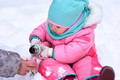 Little girl in a pink jumpsuit walks in a snowy winter park royalty free stock photo