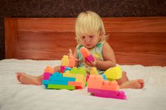 little girl in pink looks with interest at toy constructor Royalty Free Stock Photography