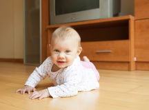 Little girl in pink lying on the floor. stock image