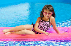 Little girl on a pink mattress. With a swimming pool royalty free stock photo